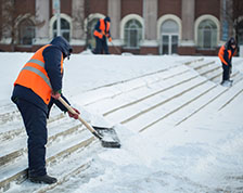 Worker outside in winter shoveling